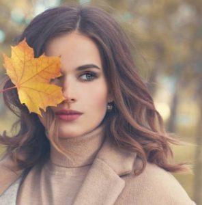 карсива жена прикрито лице с листо от дърво клен