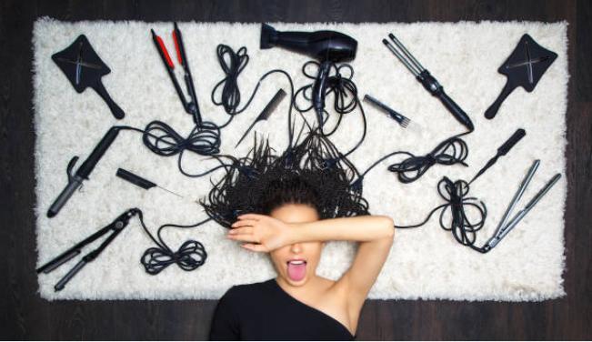 момиче с различни уреди за оформяне на прически - сешоари, преси, четки, маши