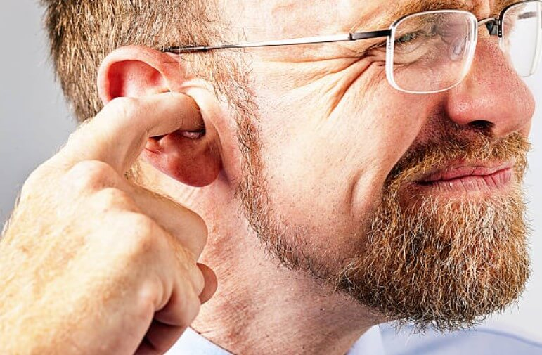 мъж с пръст в ухото
