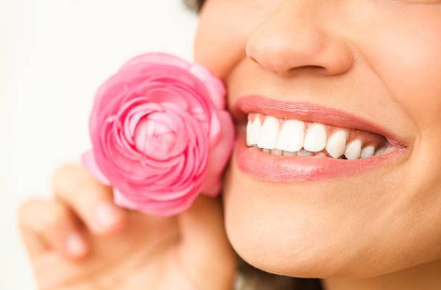 усмихната жена, бели зъби и роза