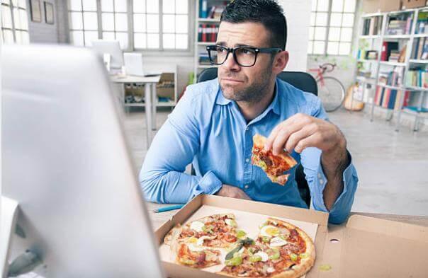 Мъж, който яде пица в офис