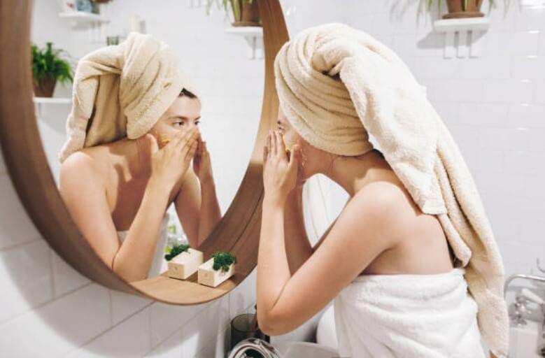 момиче, масажиращо лицето си пред огледало