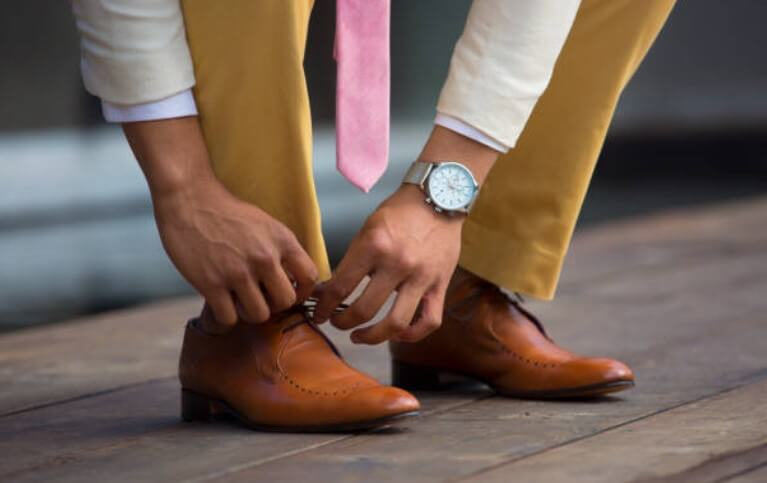 мъж завръзва обувките