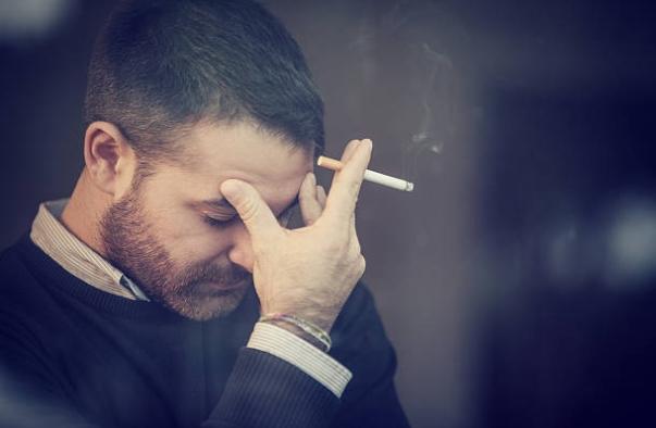 замислен мъж пуши цигара