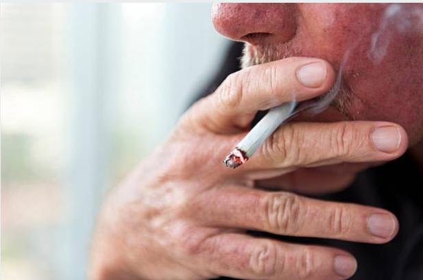 възрастсен мъж пуши цигара